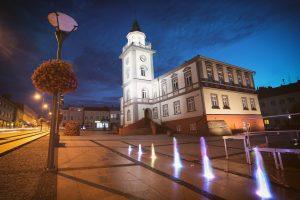 Ratusz w porze nocnej, przed budynkiem podświetlane fontanny