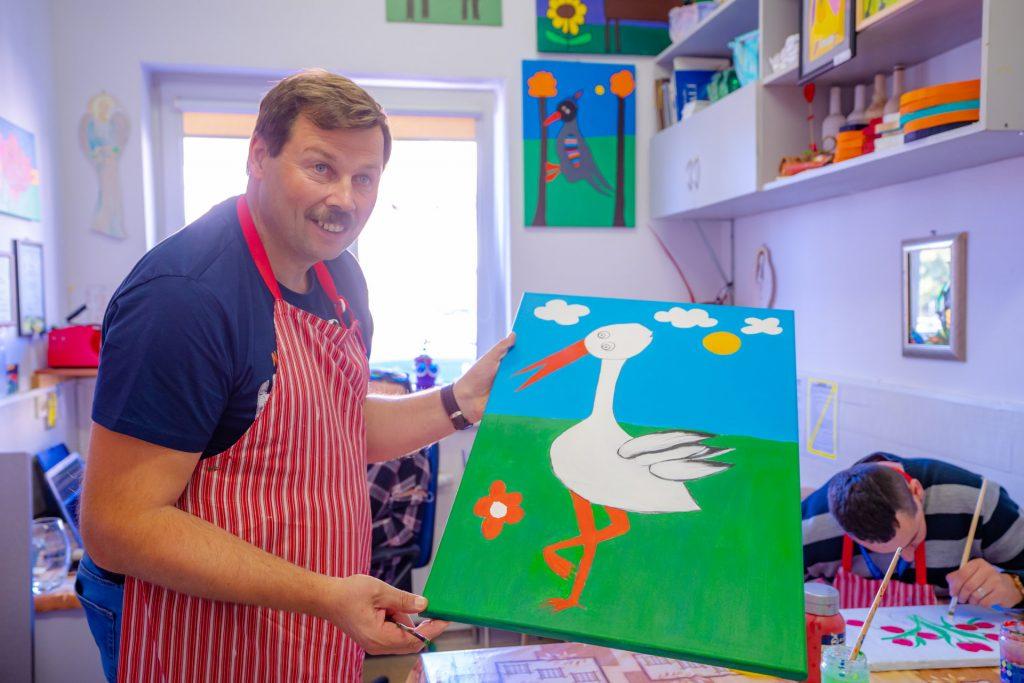 Mężczyzna w fartuchu w paski prezentuje obraz z namalowanym bocianem