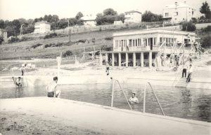 Czarno-białe zdjęcie otwartego basenu kąpielowego. W głebi budynek