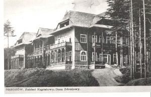Czarno-białe zdjęcie budynku w stylu góralskim, ze spadzistym dachem