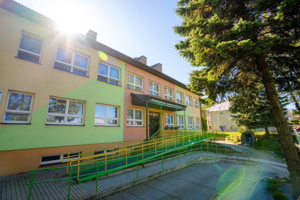 Dwukondygnacyjny budynek przedszkola z podjazdem dla wózków inwalidzkich. Elewacja budynku kolorowa.