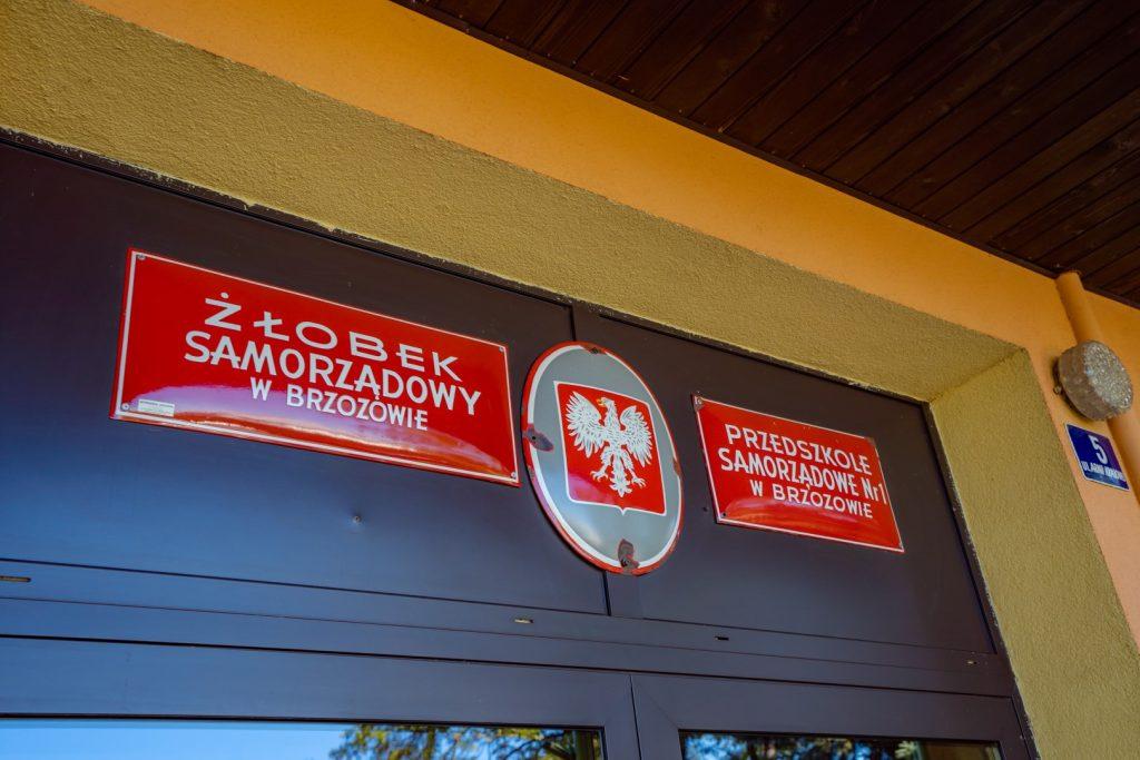 Szyldy żłobka i szkoły na czerwonym tle, zawieszone nad wejściem
