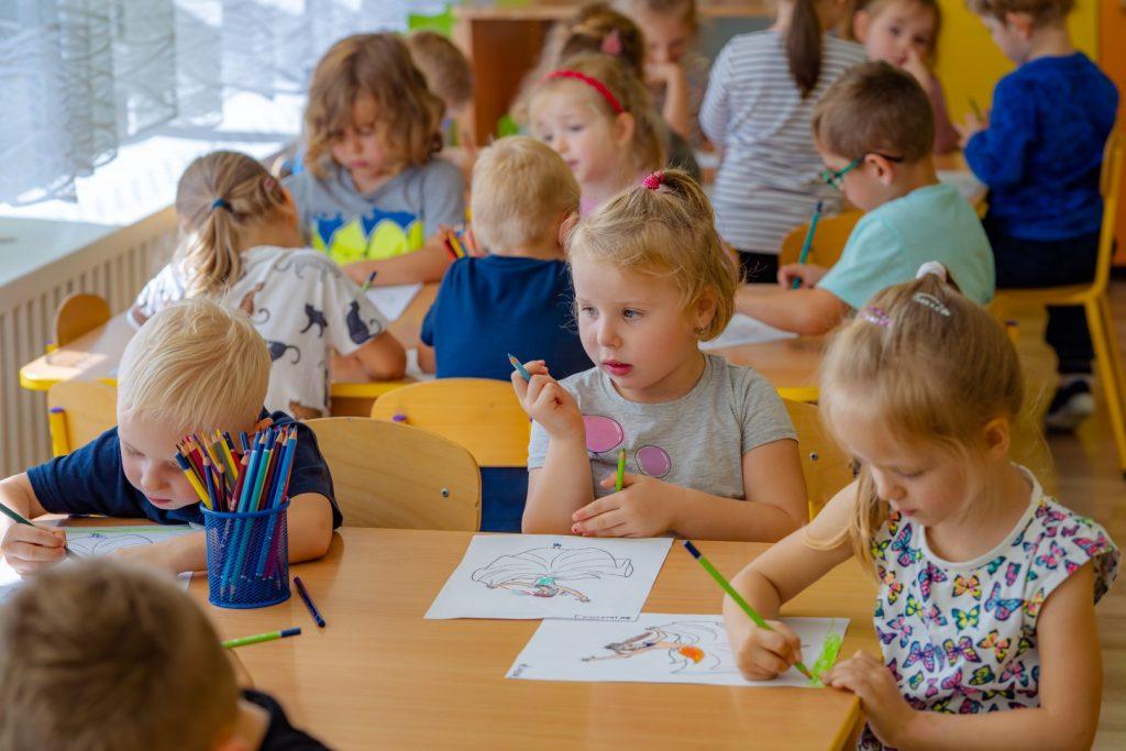 Dzieci siedzą przy stołach i rysuja na kartkach