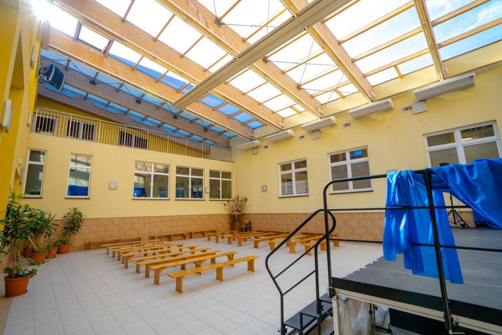 Patio z przeszklonym dachem. Na podłodze ławli oraz scena. Ściany w kolorze żółtym