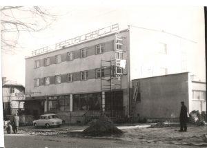 Czarno-białe zdjęcie z budowy hotelu i restauracji. Przed budynkiem stoi samochów