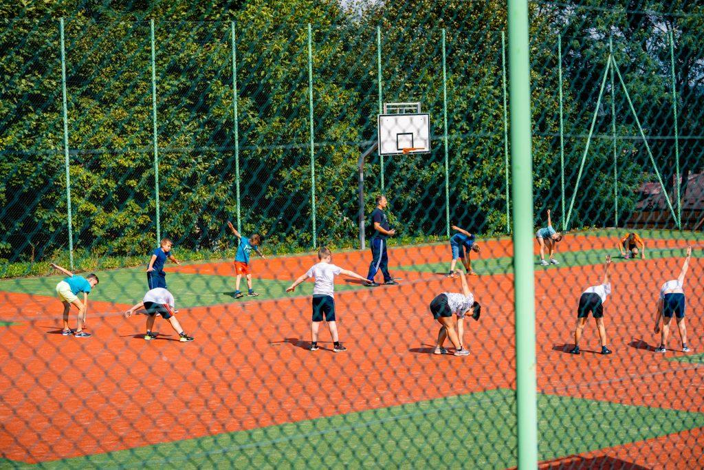 Cjłopcy w strojach sportowych ćwiczą na boisku. Boisko jest ogrodzone wysoką siatką.