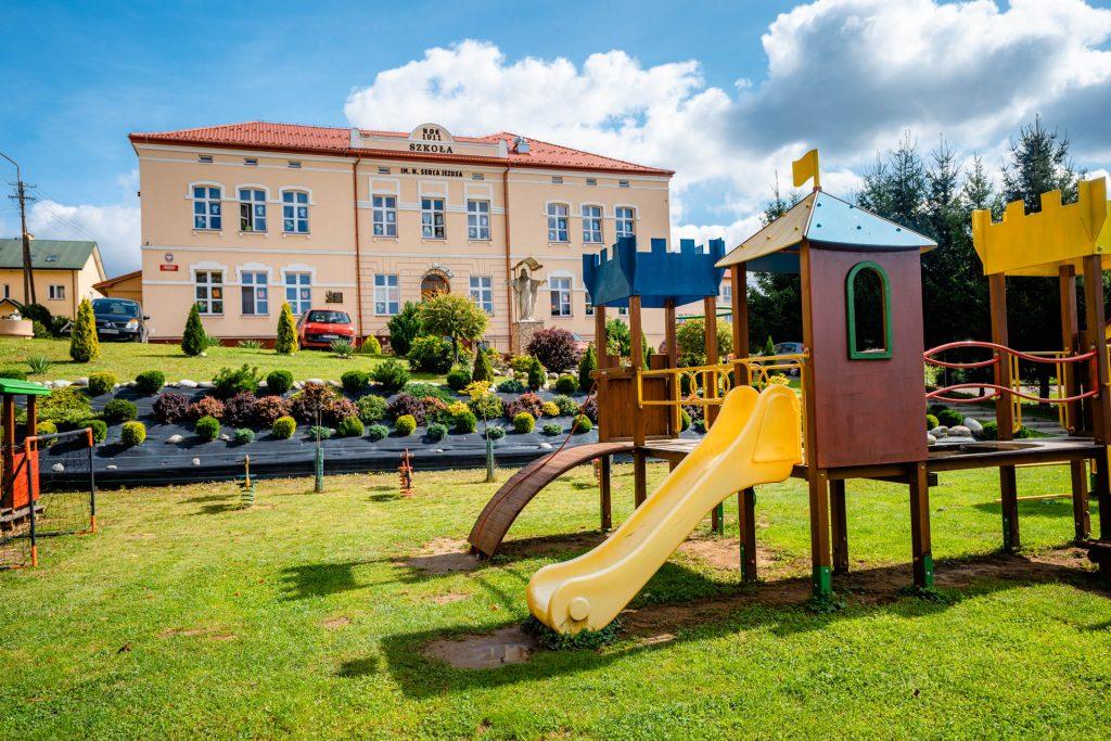 Plac zabaw wśród zieleni. W głębi różowy budynek ze spadzistym dachem