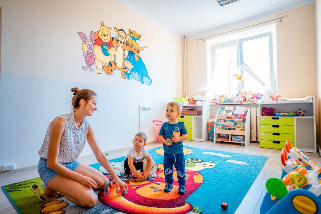 Dwójka dzieci, obok klęcząca kobieta. Grupa znajduje się w kolorowej sali żłobka