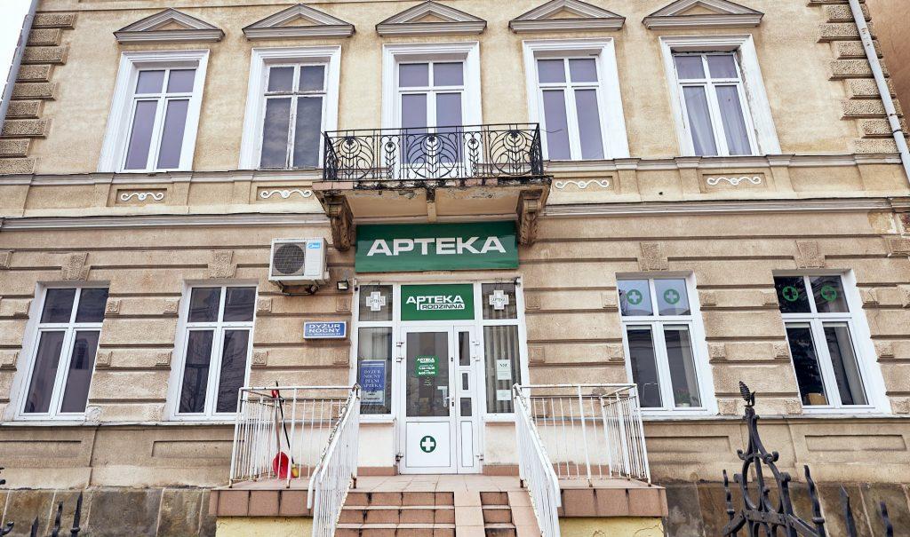 """Stylowy, dwukondygnacyjny budynek. Nad wejściem biały napis """"Apteka"""" na zielonym tle"""