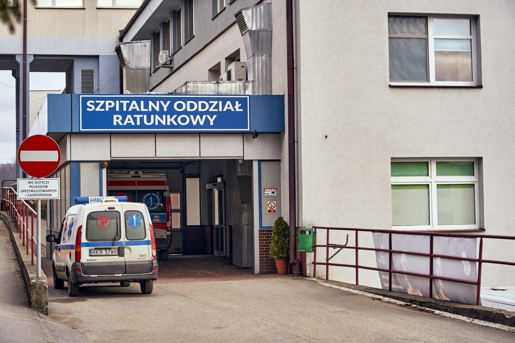 """a budynku biały napis """"Szpitalny Oddział Ratunkowy"""" na niebieskim tle. Przed budynkiem karetka pogotowia"""