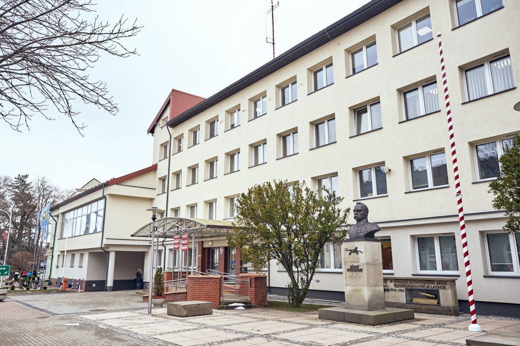 Czterokondygnacyjny budynek urzędu z jasną elewacją. Przed budynkiem popiersie i drzewa