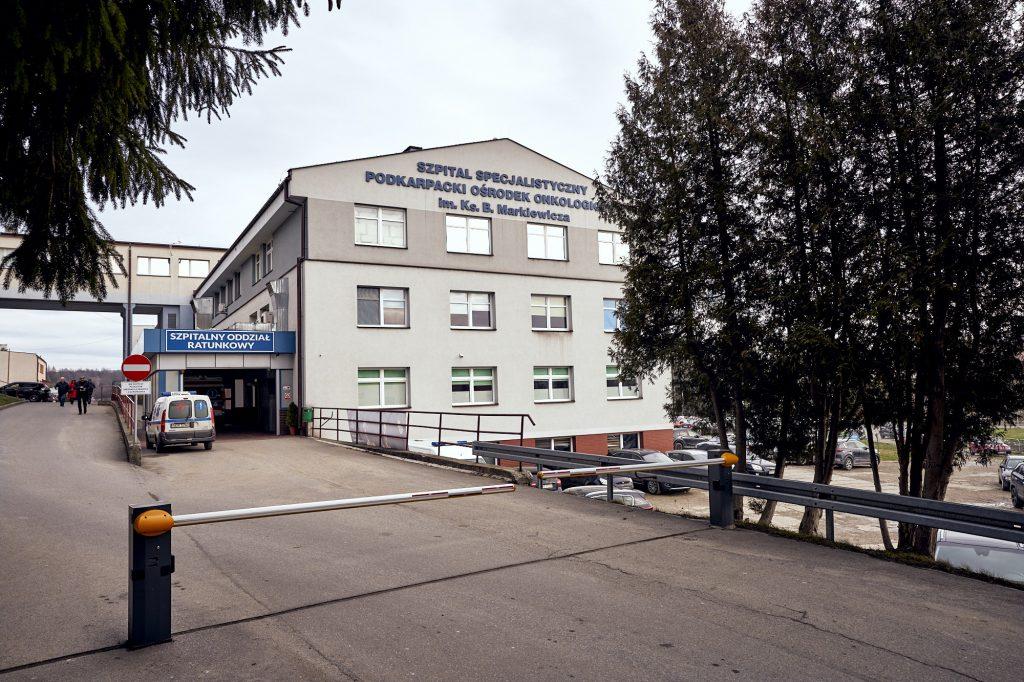 Podjazd pod budynek szpitala zagrodzony szlabanem. Przed budynkiem karetka pogotowia