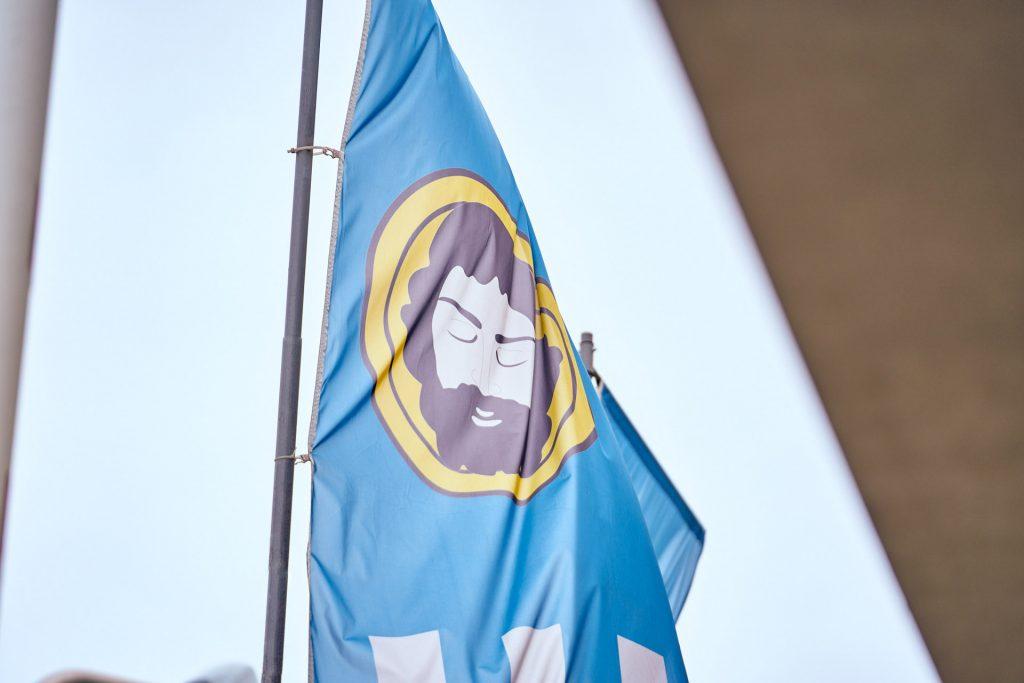 Błękitna flaga na szarym maszcie. Na fladze twarz Chrystusa na żótym tle