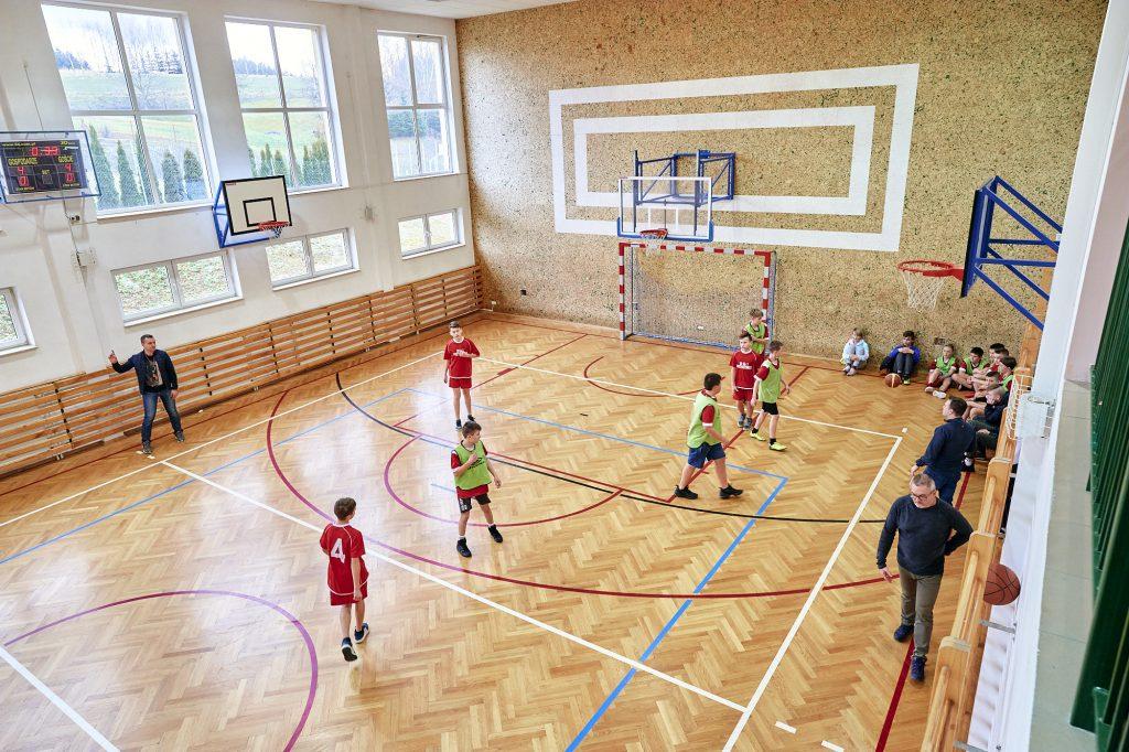 Mecz piłki ręcznej na sali sportowej. Piłkarze w strojach czerwonych i seledynowych