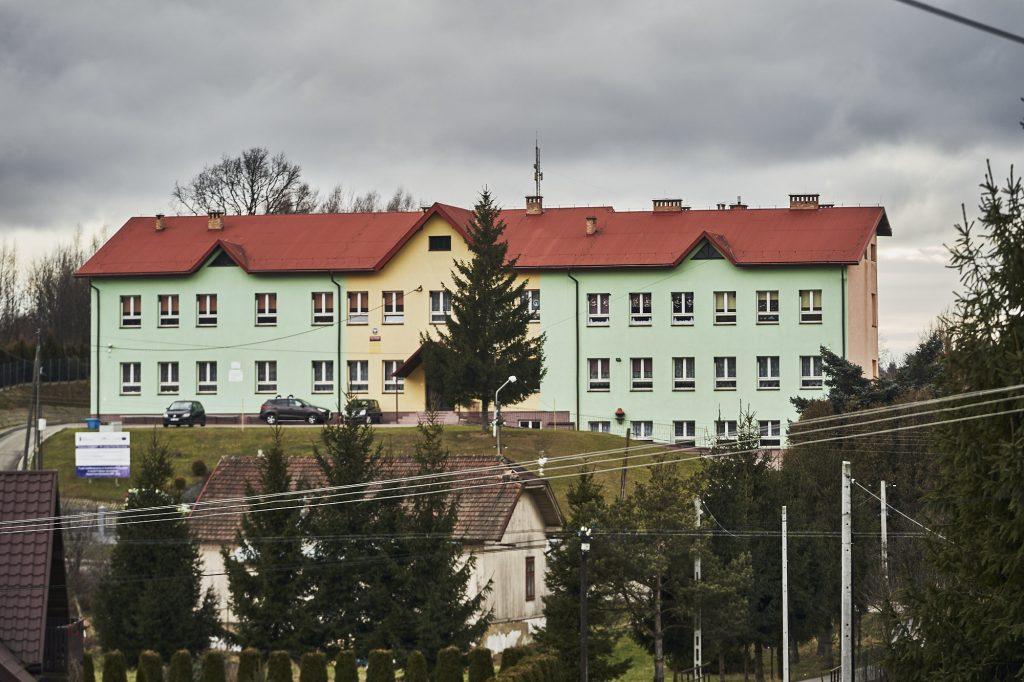 Budynek szkolny w kolorze żółtym i seledynowym. Przed budynkiem stoja trzy samochody