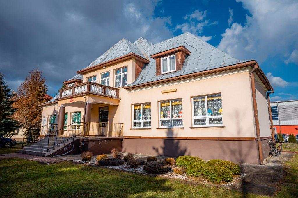 Dwukondygnacyjny budynek z srebrnym spadzistym dachem. Do wejścia prowadzą schody, nad wejściem balkon oparty na brązowych kolumnach