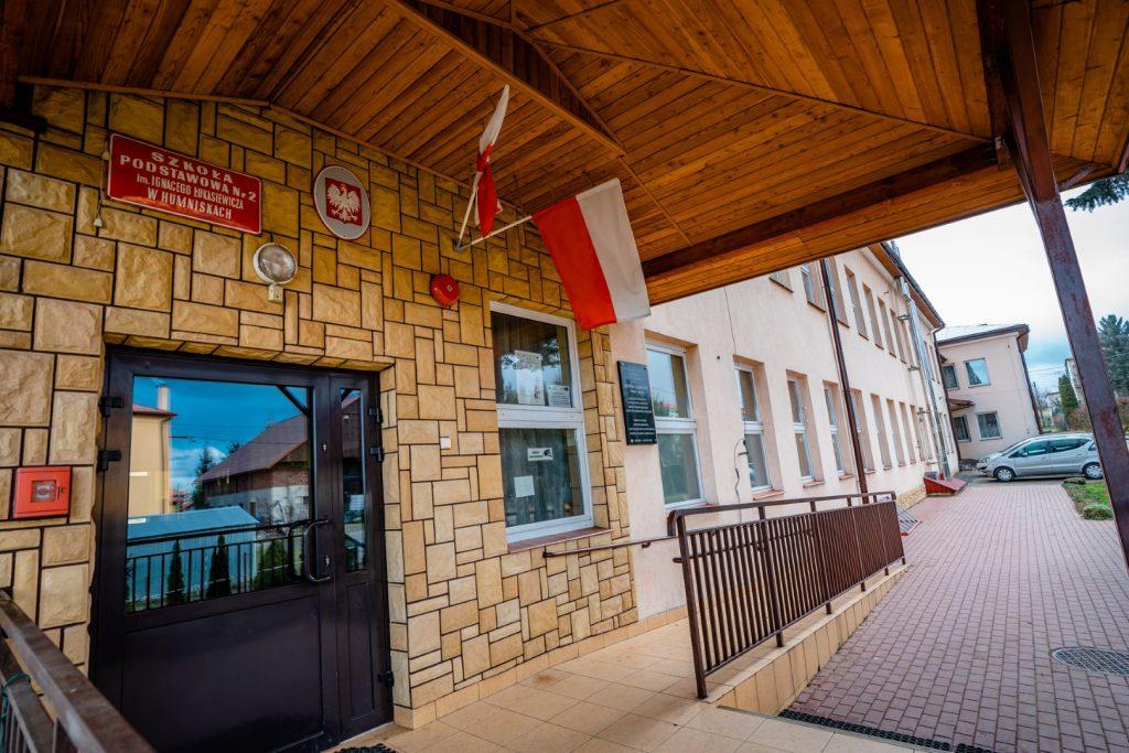 Oszklone drzwi prowadzące do szkoły. Nad wejściem czerwona tablica z białymi literami oraz godło Polski