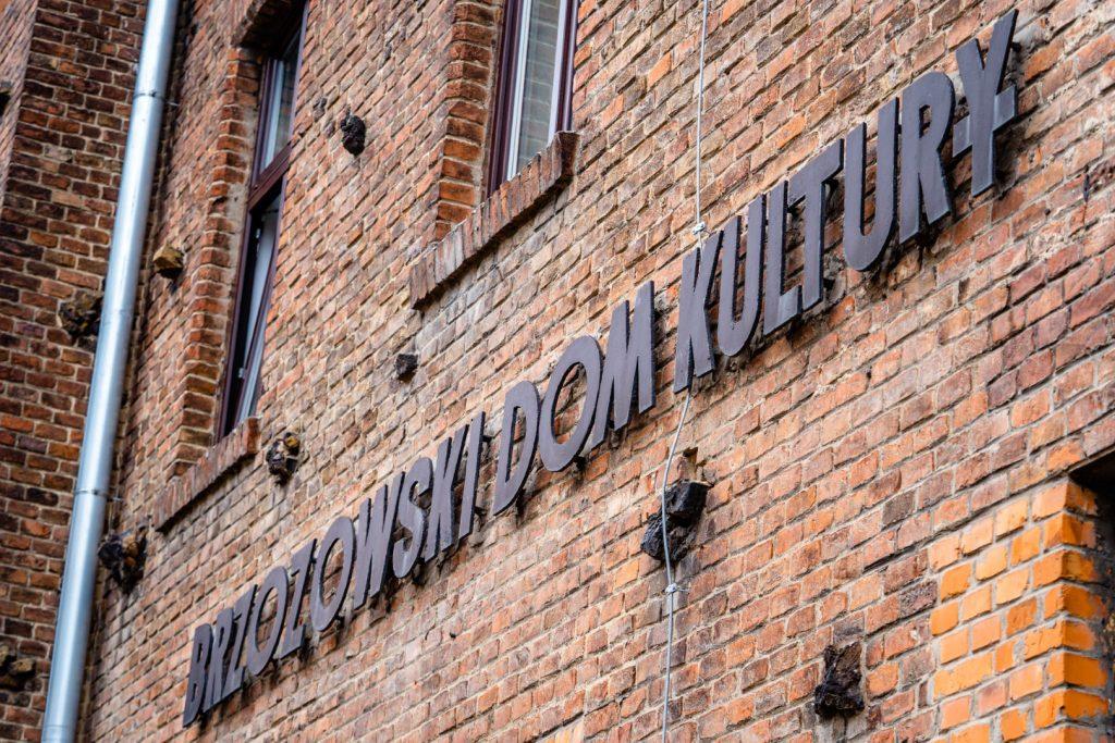 Ściana budynku zbudowanego z czerwonej cegły. Na urze napis z czarnych liter : Brzozowski Dom Kultury