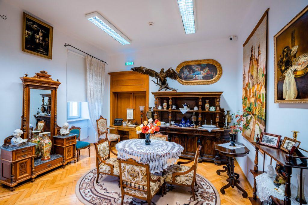 Pokój umeblowany w meble najprawdopodobniej z początku XX w. Na środku okragły stół nakryty białym koronkowym obrusem