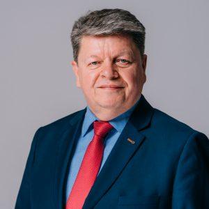 Siwiejący meżczyzna w średnim wieku, ubrany w granatową marynarkę, niebieską koszulę i czerwony krawat