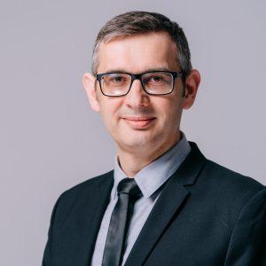 Meżczyzna w średnim wieku w okularach, ubrany w czarną marynarkę, szarą koszulę i szary krawat