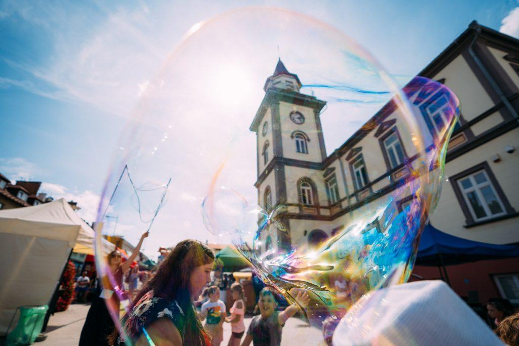 Młodzież puszcza wielkie bańki mydlane na placu przed ratuszem z wieżą