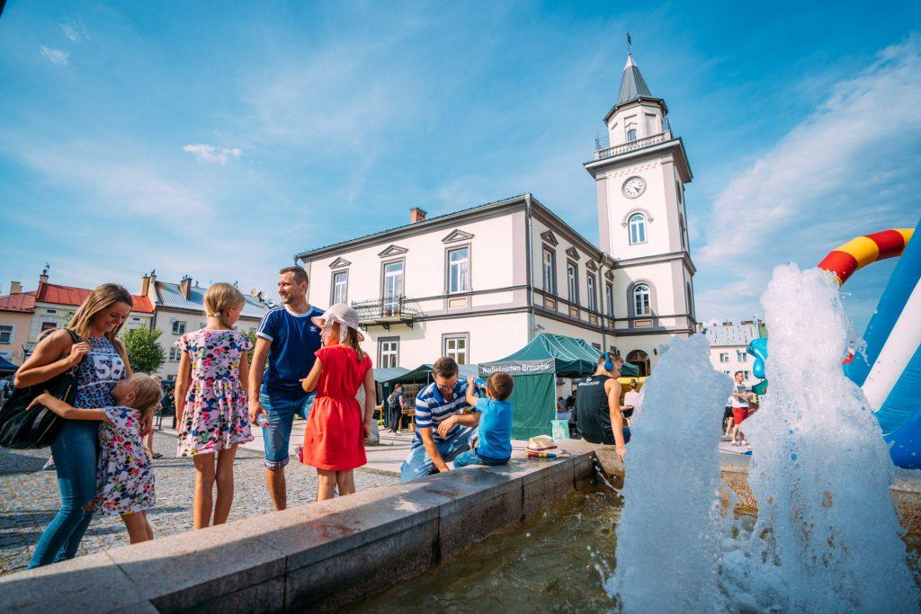 Ludzie w różnym wieku, w kolorowych letnich ubraniach przebywają na placu z fontanną. W głebi budynek ratusza