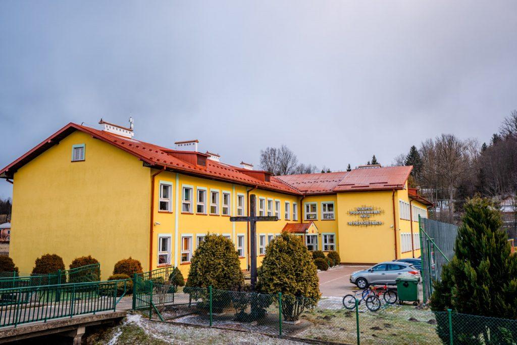 Dwukondygnacyjny budynek szkoły w kolorze żółtym pokryty czeerwonym spadzistym dachem. Przed budynkiem samochód, rowery i drewniany krzyż