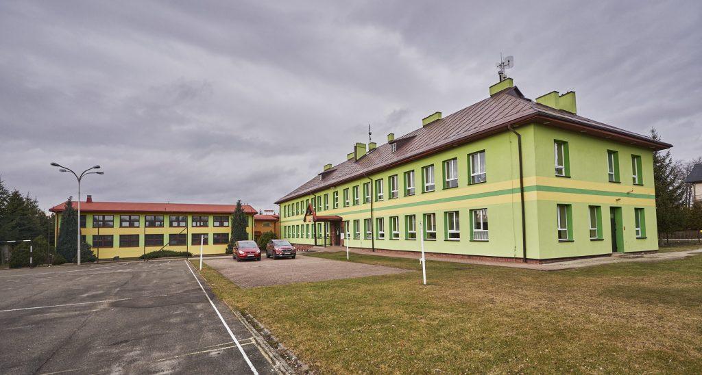 Budynek szkoły z zieloną elewacją i brązowym dachem. Przed szkołą stoją dwa samochody