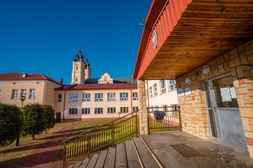 Wejście do budynku szkolnego. W głębi inne budunki i barokowy kościół z dwoma wieżami