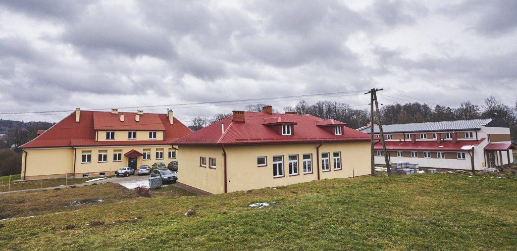 Budynki szkolne z czerwonymi dachami. Ściany elewacji pomalowane na żółto. Z boku biało-brązowy budynek z blaszanym dachem