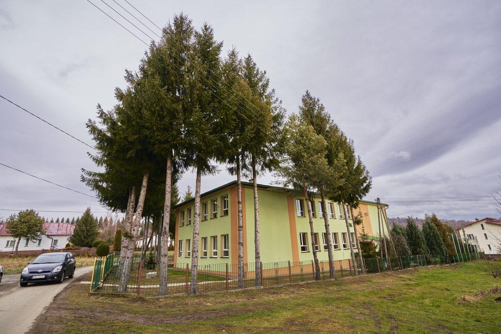 Budynek szkoły otoczony drzewami z elewacja koloru pomarańczowego i zielonego