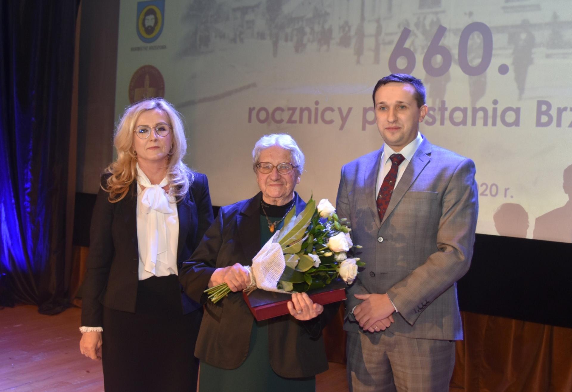Dwie kobiety i mężczyna stoją na scenie. Kobieta w środku trzyma bukiet białych róż