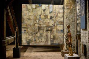 Duży abstrakcyjny obraz zawieszony w starym wnętrzu. Po bokach dwie drewniane rzeźby