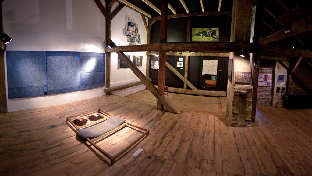 Wnętrze galerii dzieł sztuki z podłoga z drewnianych desek. Sufit podparty jest drewnianymi filarami
