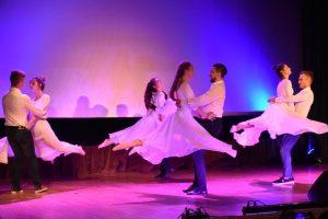 Pary tańczące na scenie. Panie w długich białych sukniach, a panowie w biaych koszulach i ciemnych spodniach