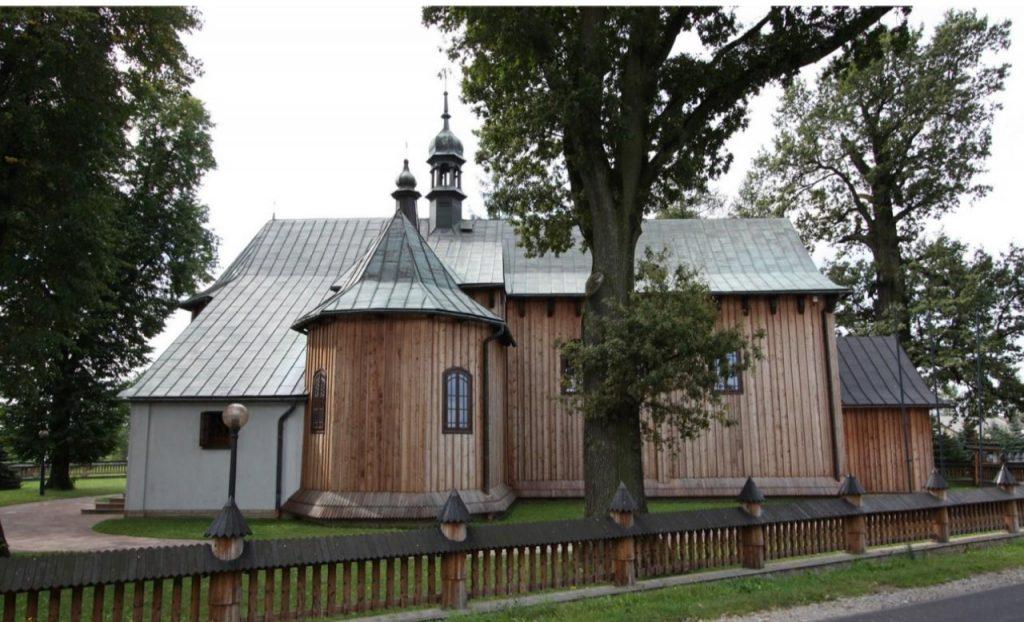 Zabytkowy kościół z jasnego drewna, kryty blaszanym dachem. Przed kościołem duże drzewa liściaste.