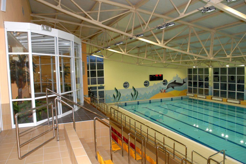 Kryty basen pływacki z trybunami dla widzóa. Na ścianiekolorowe malunki