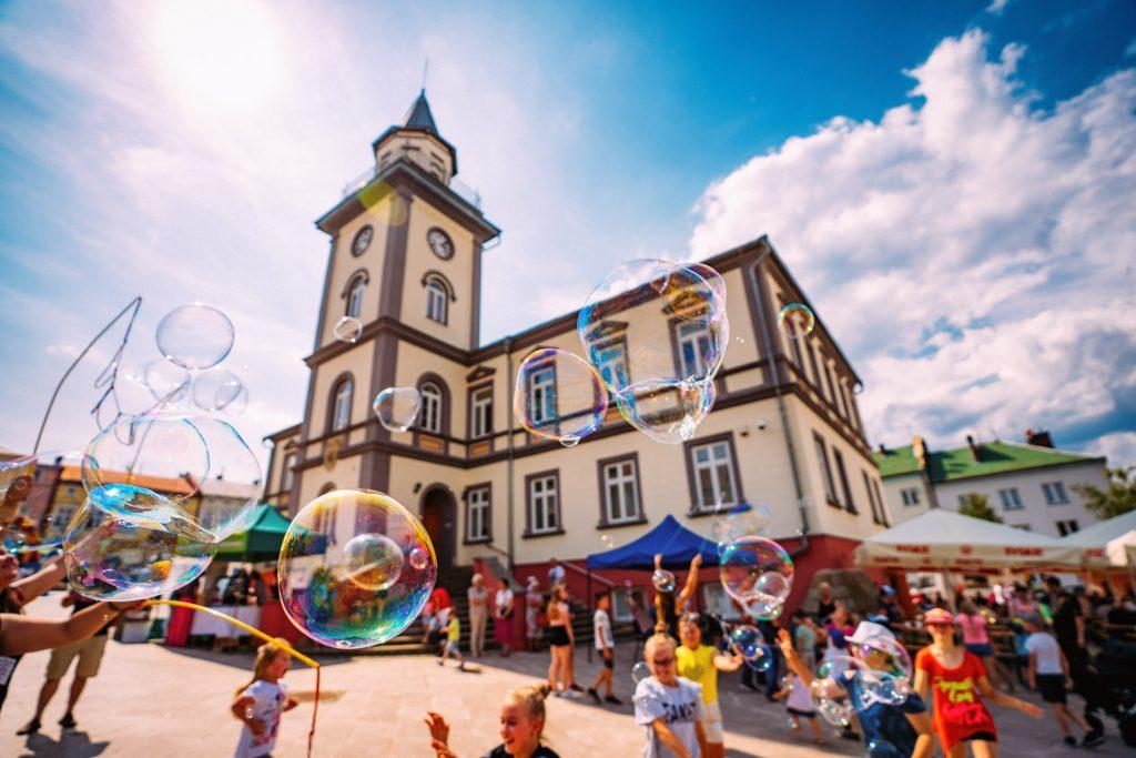 Dzieci bawią się dużymi bańkami mydlanymi przed budynkiem z wieżą