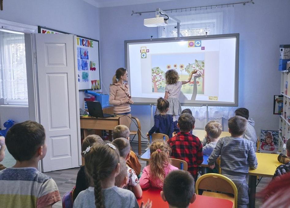 Grupa dzieci w szkole. Jedna dziewczynka korzysta z tablicy interaktywnej.